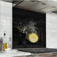 Fond de hotte noir avec rondelle de citron jaune plongée dans l'eau